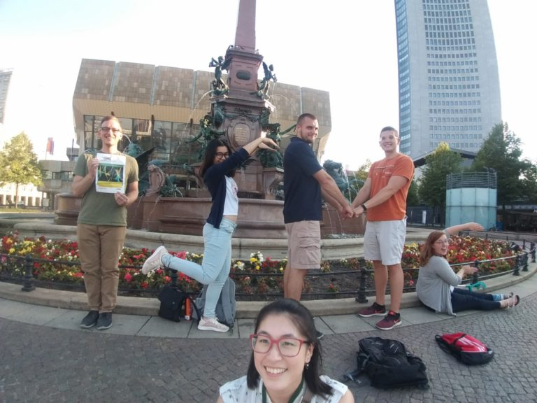 "MDTP students enjoying Leipzig, Germany at the 17th International Symposium on Microbial Ecology. They spelled out ""ISME"" in a creative but unsuccessful attempt to win free conference registration. I: Alex LaReau. S: Chutikarn Chitboonthavisuk. M: Andrew Steinberger and Joe Skarlupka. E: Madison Cox. Bottom/Mastermind: Edna Chiang."