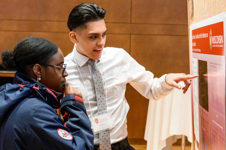 Students discuss poster at undergrad symposium